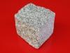 Kostka granitowa, cięto-łupana (przynajmniej jedna powierzchnia cięta). Polski granit, szary średnioziarnisty